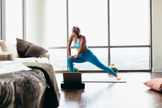 Black woman doing virtual yoga session at home