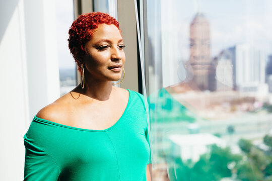Black Woman looking out window thinking and reflecting at home