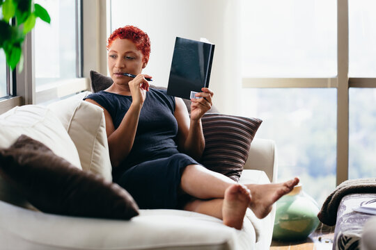 Black woman reading a book at home during pandemic