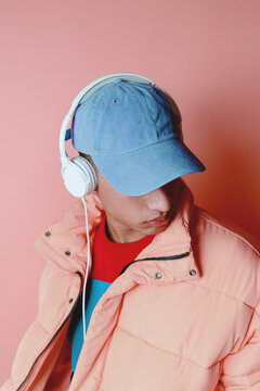 Portrait of a young man listening music with pink coat over pink background.