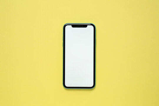 MYKOLAIV, UKRAINE - JULY 07, 2020: iPhone 11 on yellow background, top view. Mockup for design
