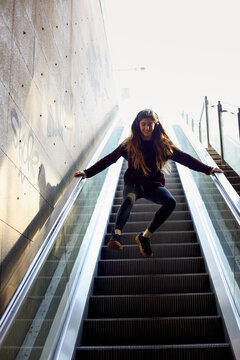 Young woman playing and jumping on the metro stairways