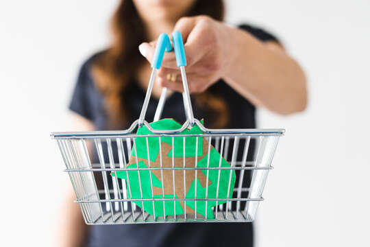 woman holding a shopping basket with recycle sign towards the camera, sustainable development and consumer buying habits