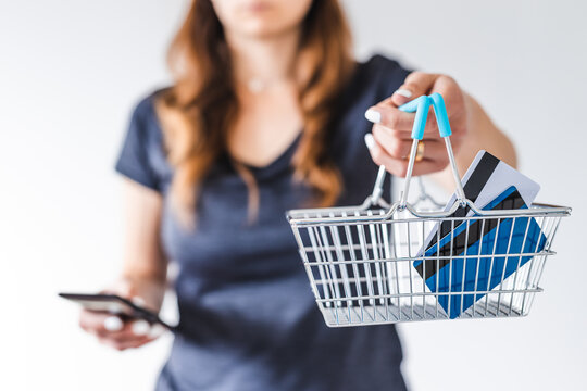 woman holding shopping basket with credit cards towards the camera and checking her smartphone to decide on what to buy, influencer marketing or product reviews