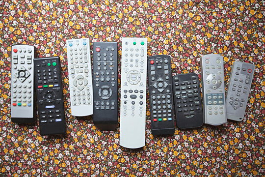 Collection of old television, dvd, video remote controls on flower table cloth