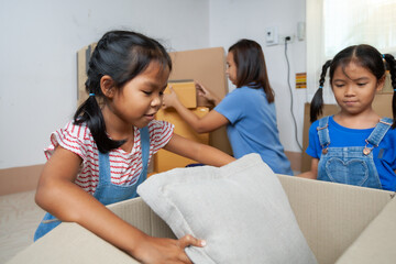 Two asian child girls helping parents put on stuff into the box on moving day. Home renovation and relocation concept.