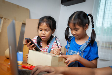 Woman hand using notebook computer taking receive and checking online purchase shopping order. Child is writing address into the box to help parent prepares delivery box for the online customer.