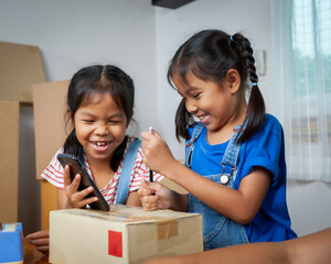 Two child girls helping parent to write customer address into the box to prepare delivery box for the online customer with fun and happy