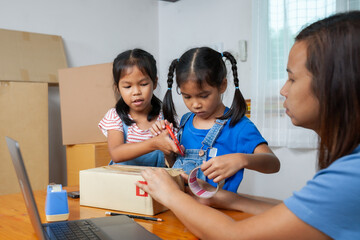 Two child girls helping parent to pack the product and use a Scotch tape to tape a box before delivery to online customer with fun and happy.