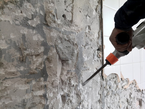 Construction worker using a handheld demolition of old tiles with jackhammer. Renovation of old walls in the bathroom.