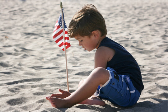 Young boy plays with American Flag on the beach