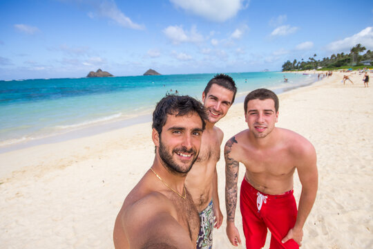 Three young male friends taking a selfie on a tropical beach on summer