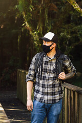 Young tourist wearing face mask on outdoor destination. Travel and coronavirus concept