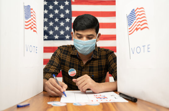 Young man in medical mask busy inside the polling booth with US flag as background - Concept of in person voting with covid-19 safety measure at US election.