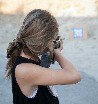 Teen girl shooting a pellet gun at a target in the sand