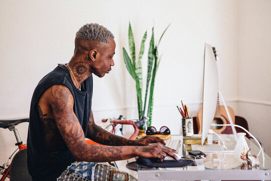 Black young man with tattoos working at his desk.