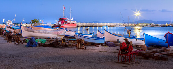 Pomorie, Bulgaria beachfront sea panoramic banner with boats in the town and seaside resort on Black sea, blue hour dusk view Wall mural