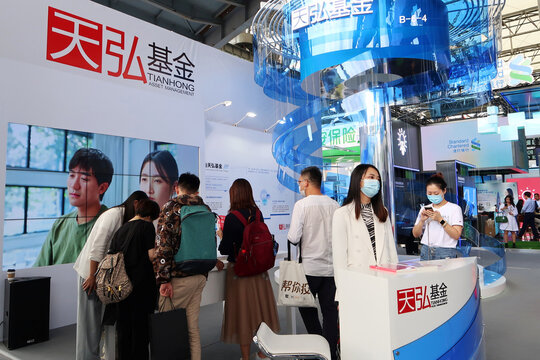 People wearing face masks following the coronavirus disease (COVID-19) outbreak are seen at the booth of Tianhong Asset Management at a fair during the INCLUSION fintech conference in Shanghai