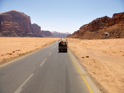 Tourists traveling in a jeep by the Jordanian desert of Wadi Rum