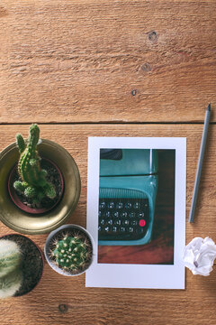 Old typewriter photo on a table with some cactus and one pencil.