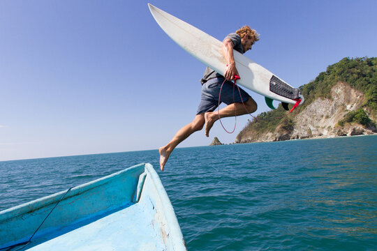 Surfer jumps off a boat with his surfboard