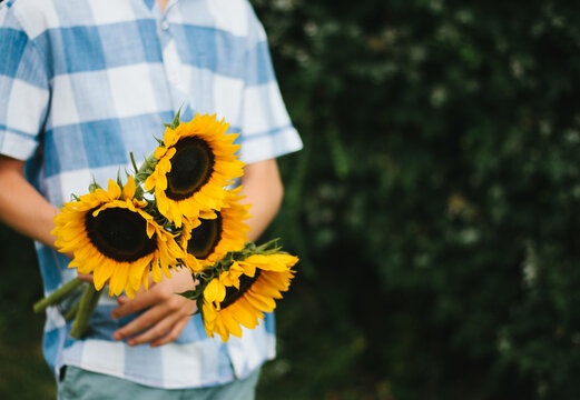 Teenager holding a bunch of sunflowers