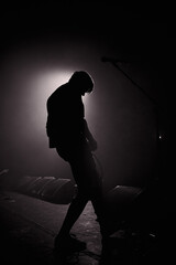 Monochrome photography. A slightly blurred silhouette of a young man with a guitar in the smoke, illuminated by a contour light.