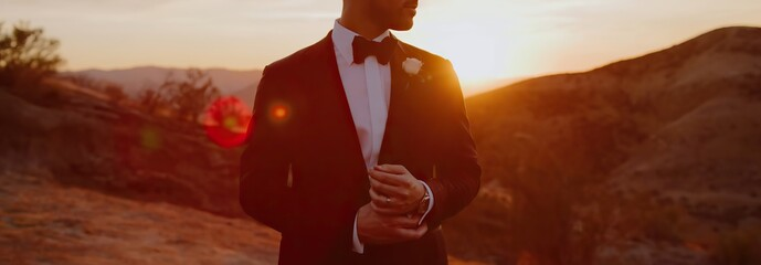 Groom in tuxedo, white shirt and bow tie at sunset