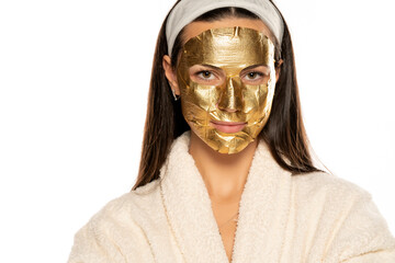 young woman posing with golden mask on her face