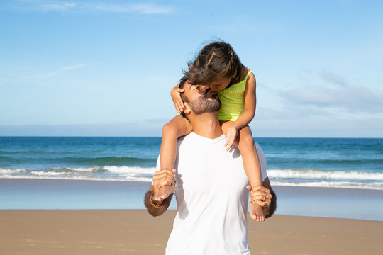 Adorable little girl kissing her dad while riding on his neck. Father and daughter walking or standing on beach by sea. Medium shot. Family leisure time concept