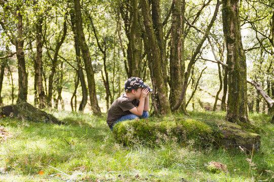 Little boy exploring the woods with his binoculars