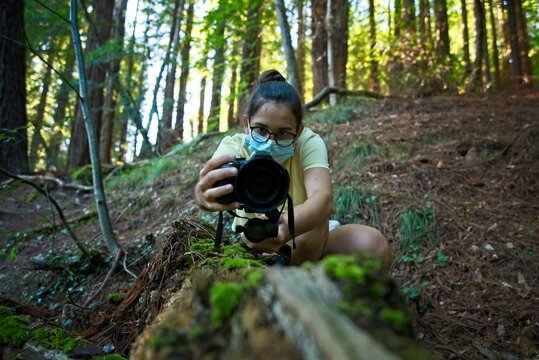 A teenage girl wearing a mask shoots video with her camera on a trunk in the forest