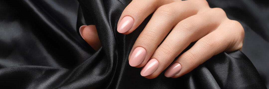 Rose nail polish manicure. Woman hand on black fabric background. Advertising banner ad.