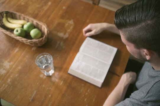 Boy reading Holy Bible on the table