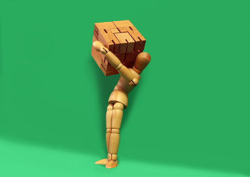 Mannequin carries wooden box on one shoulder. Close up of the wooden puppet holding box in front of green background with copy space.