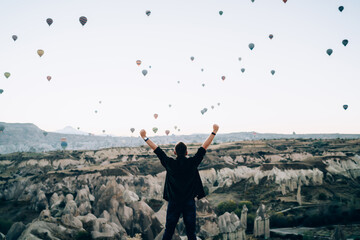Faceless motivated man raising arms up against hot air balloons