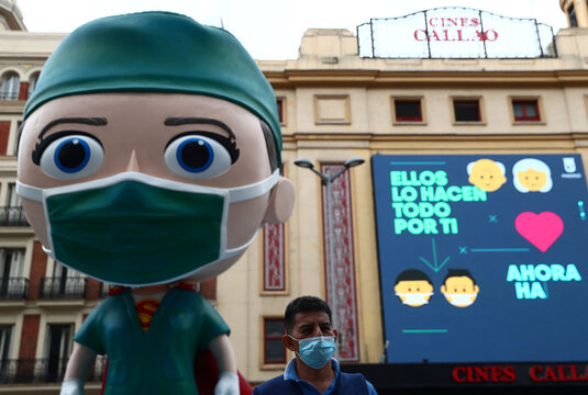 A man wearing a protective face mask poses for a picture next to an oversized model of a health worker in Madrid