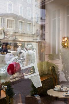 Woman sat in cafe reading newspaper, Salzburg, Austria