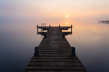 A jetty in a lake during a tranquil, foggy dawn.