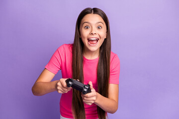 Photo portrait of young schoolgirl playing video games holding gamepad with both hands screaming...