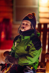 Boy in snow clothes eating a marshmallow just toasted over a campfire at night