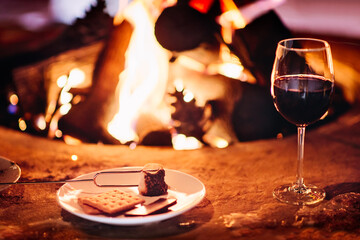 S'mores and a glass of red wine beside a camp fire at night