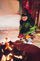 Boy toasting marshmallows over a camp fire at night surrounded by snow in winter
