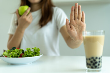 A woman's hand is pushing a glass of milk tea, pearls and eating green apples with vegetable salad. The concept of good health control, diet