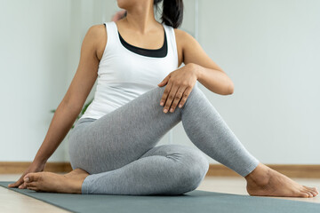 Young woman doing stretching exercises at home in relaxation. Women are doing seated twist exercises for health and a firmer body. The concept exercise and a healthy life.