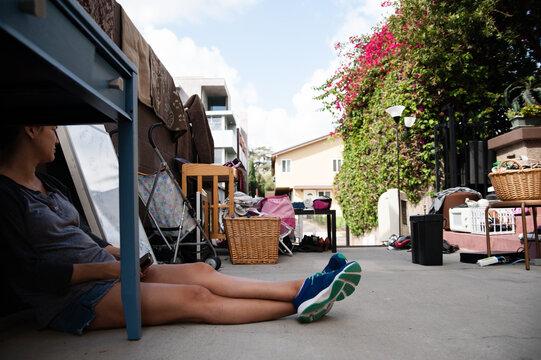 woman sitting among junk at yard sale