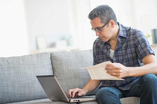 Man doing home finances with laptop