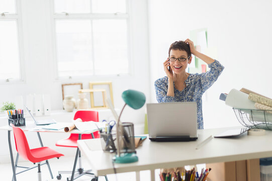 Senior business woman using cell phone in office