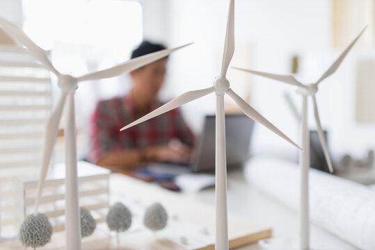 Wind turbine models on desk, architect in background