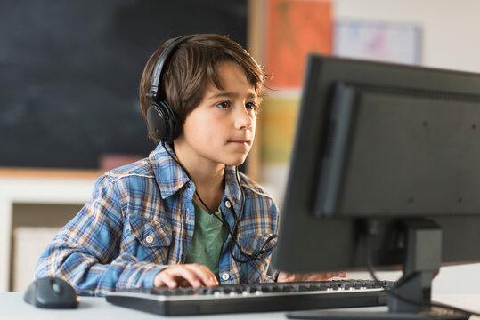 Schoolboy (6-7) using computer in classroom